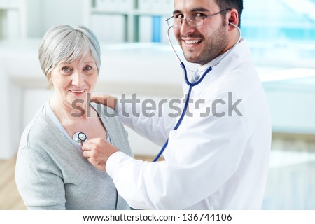 Confident doctor examining his senior patient while both looking at camera - stock photo