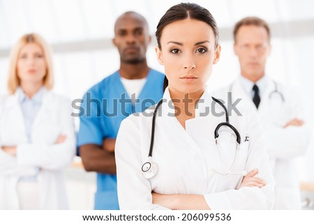Confident doctor leading her team. Beautiful female doctor keeping arms crossed and looking at camera while her colleagues standing behind her in the background - stock photo