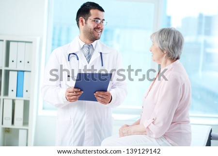 Confident doctor with stethoscope and clipboard interacting with his senior patient in hospital - stock photo