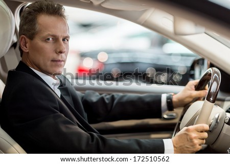 Confident drive. Side view of confident senior man in formalwear sitting in car and looking at camera - stock photo