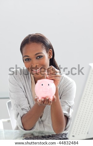 Confident ethnic businesswoman saving money in a piggybank at her desk