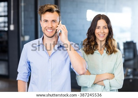 Confident executive talking on phone with female colleague standing beside in office - stock photo