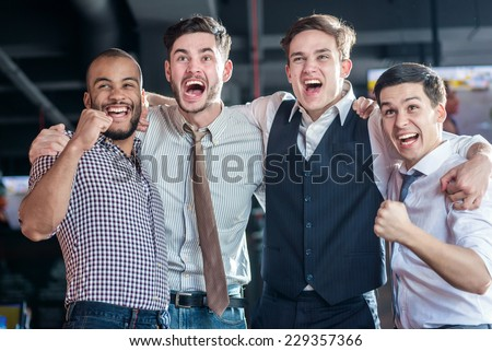 Confident fans watching TV and delight football. Four successful men shout and rejoice football meeting. Friends having fun together watching TV - stock photo