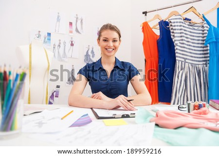 Confident fashion designer. Attractive female fashion designer looking at camera and smiling while sitting at her working place - stock photo