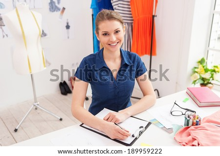 Confident fashion designer. Top view of attractive female fashion designer sketching and looking at camera while sitting at her working place - stock photo