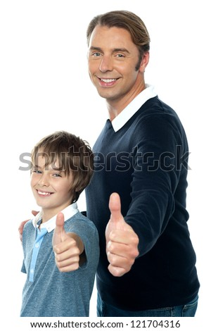 Confident father and son duo  gesturing thumbs up sign. Smiling faces - stock photo