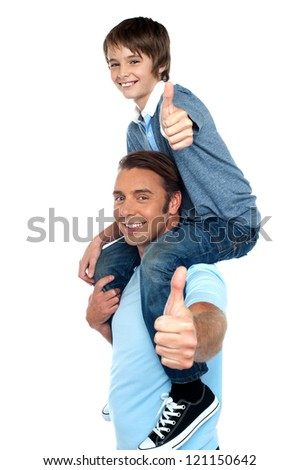 Confident father carrying his son on shoulder. Both gesturing thumbs up to camera. - stock photo