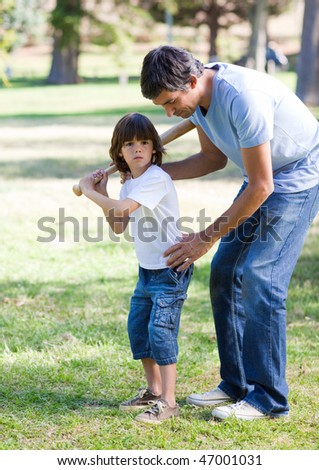 Confident father playing baseball with his son in the park - stock photo