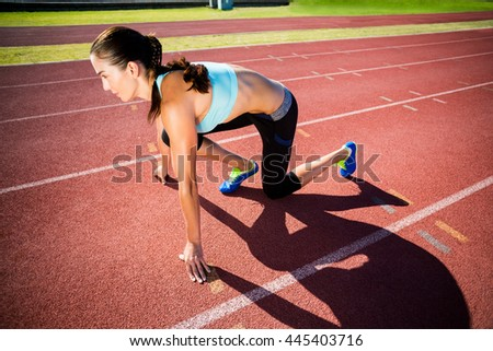 Confident female athlete in ready to run position on running track - stock photo