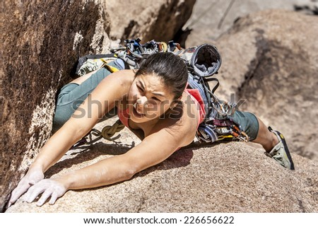 Confident female climber struggles for her next grip on the edge of a challenging cliff. - stock photo