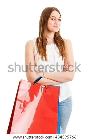 Confident female customer doing shopping and standing with arms crossed and carrying shopping bags isolated on white - stock photo