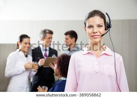 Confident Female Customer Service Representative Standing At Off - stock photo