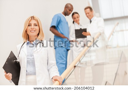 Confident female doctor. Confident female doctor moving downstairs and smiling while her colleagues talking in the background - stock photo