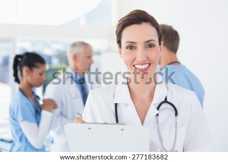 Confident female doctor holding clipboard in medical office - stock photo