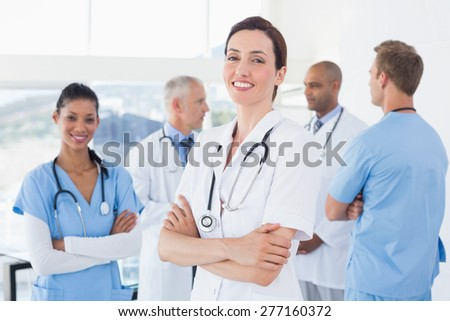Confident female doctor smiling at camera with her team behind in medical office