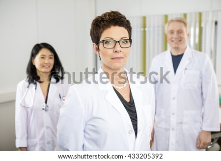 Confident Female Doctor Standing With Colleagues In Hospital - stock photo