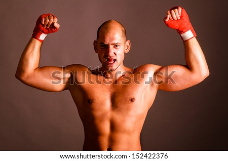 confident fighter is showing biceps on dark background - stock photo