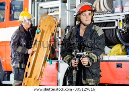 Confident firefighter looking away while holding hose with colleague carrying wooden stretcher by truck at fire station - stock photo