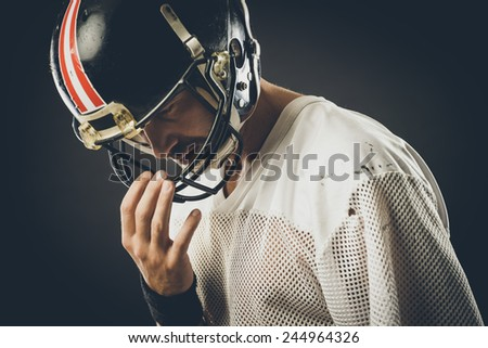 Confident football player with protective helmet posing - stock photo