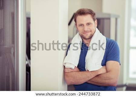 Confident friendly attractive young man at a gym posing with a towel round his neck and folded arms smiling at the camera - stock photo
