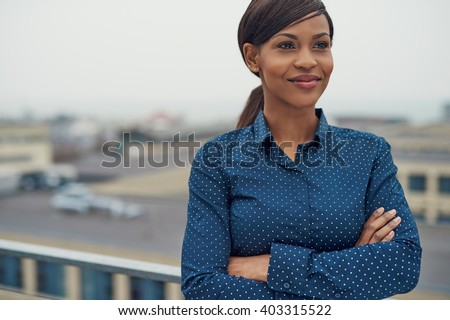 Confident friendly black business woman standing with folded arms on the rooftop of an urban commercial building smiling as she looks to the side of the camera - stock photo