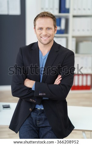 Confident friendly businessman leaning on a table in the office with folded arms grinning at the camera - stock photo