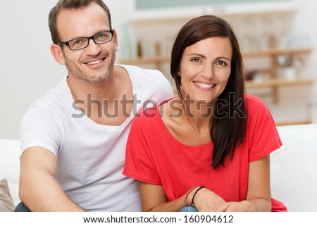 Confident friendly casual young couple relaxing at home pose side by side looking at the camera with lovely cheerful smiles - stock photo