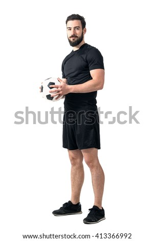 Confident futsal or football player holding ball with both hands looking at camera. Full body length portrait isolated over white background.  - stock photo