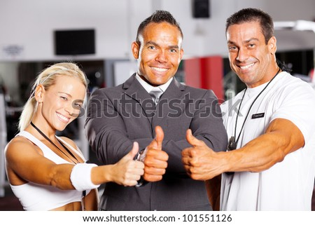 confident gym staff thumbs up - stock photo