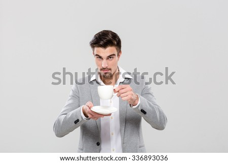 Confident handsome attractive businessman in gray jacket and white shirt drinking coffee - stock photo
