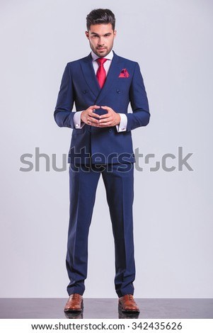 confident handsome business man posing while standing and touching his palms - stock photo