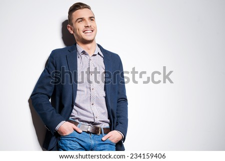 Confident handsome. Handsome young man in smart casual wear holding hands in pockets and smiling while standing against a wall - stock photo