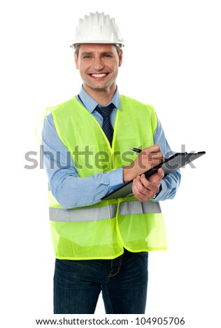 Confident handsome male architect with pen and clipboard wearing white helmet - stock photo