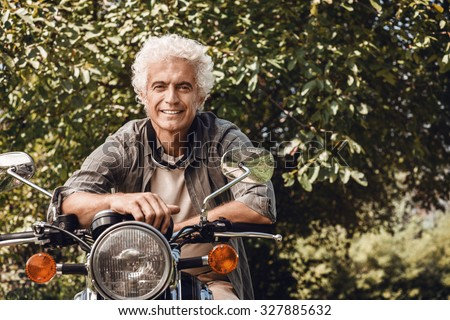 Confident handsome man riding a vintage motorbike and smiling at camera - stock photo