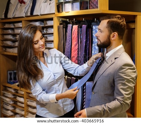 Confident handsome man with beard choosing a tie in a suit shop.