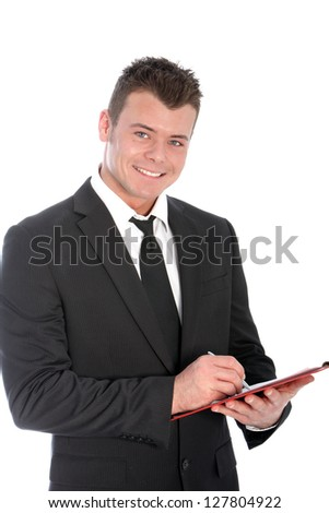 Confident handsome young businessman standing writing notes on a clipboard smiling at the camera, upper body studio portrait isolated on white - stock photo