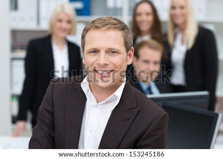 Confident handsome young businessman with a friendly smile seated in the foreground backed by his team, shallow dof - stock photo