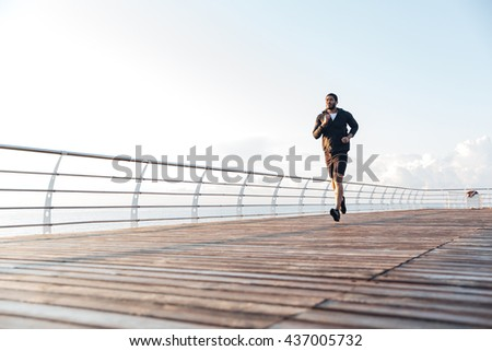 Confident handsome young sportsman listening to music and running in the morning - stock photo