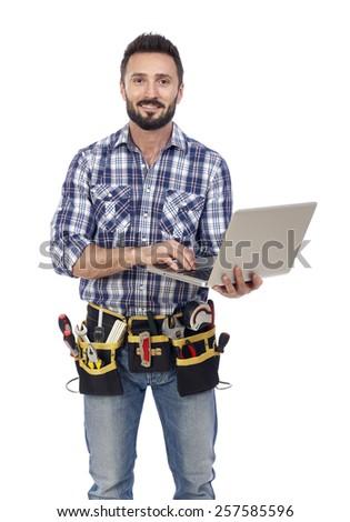 Confident handyman with laptop - stock photo