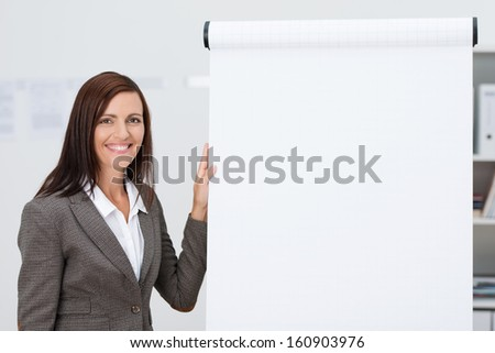 Confident happy businesswoman doing a presentation standing alongside a blank flipchart with white paper and copyspace for your text - stock photo
