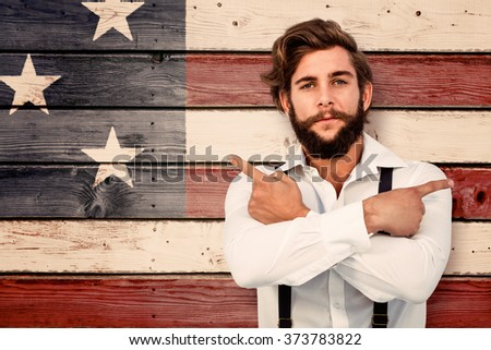 Confident hipster pointing sideways with arms crossed against composite image of usa national flag - stock photo