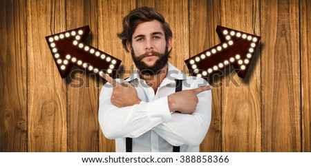 Confident hipster pointing sideways with arms crossed against wooden background - stock photo