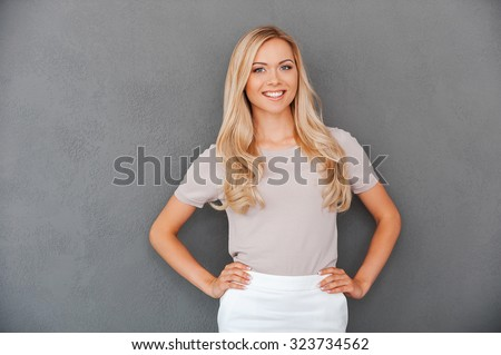 Confident in her abilities. Smiling young blond hair woman holding hands on hips and looking at camera while standing against grey background - stock photo