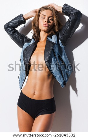 Confident in her perfect body. Beautiful young woman wearing cool jacket over the naked body and keeping eyes closed while standing against white background  - stock photo