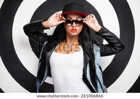 Confident in her style. Attractive young African woman in baseball cap adjusting her sunglasses while posing against black and white background - stock photo