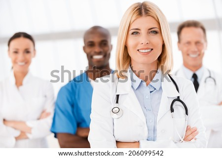 Confident in her team. Beautiful female doctor keeping arms crossed and smiling while her colleagues standing behind her in the background