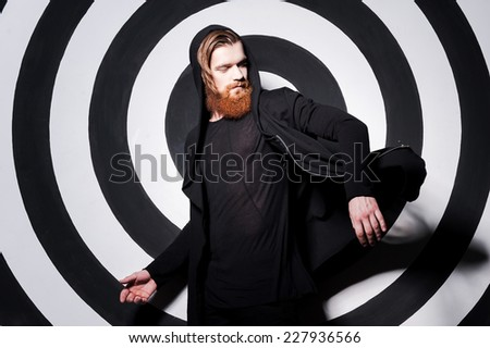 Confident in his perfect look. Handsome young bearded man adjusting his sweatshirt and looking over shoulder while standing against target background - stock photo