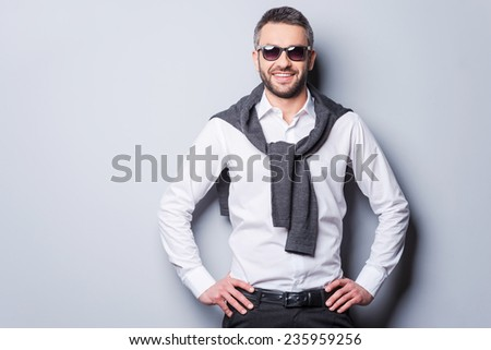 Confident in his perfect style. Handsome young man in smart casual wear and sunglasses looking at camera and smiling while holding hands on hip and standing against grey background - stock photo