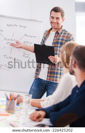 Confident in his speech. Business people in smart casual wear sitting together at the table while confident young man standing near whiteboard and pointing it with smile - stock photo