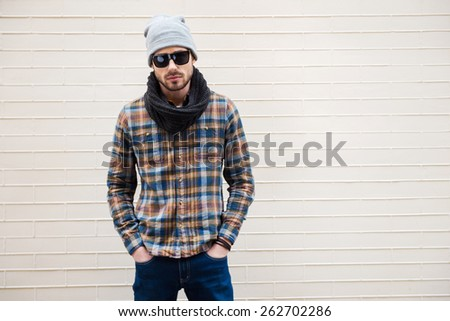 Confident in his style. Handsome young man in hat and sunglasses holding hands in pockets and looking at camera while standing against brick wall  - stock photo